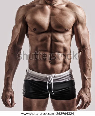 Portrait in studio of muscular male body in black swimming trunks. Isolated on grey background. - stock photo