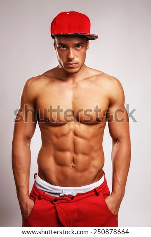 Portrait in studio of muscular male in red sport pants with white stripe on them and a red cap. Isolated on grey background. - stock photo