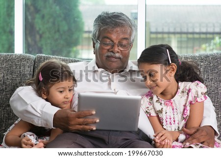 Portrait Indian family at home. Grandparent and grandchildren using digital tablet computer. Asian people living lifestyle.