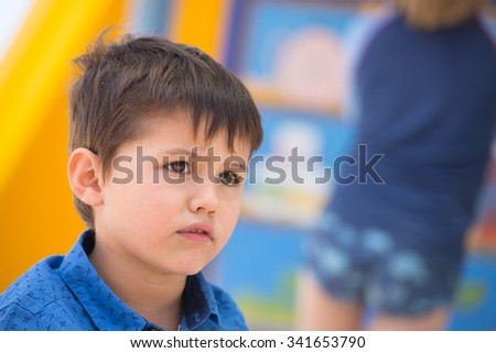 Portrait latino boy looking sad, worried and unhappy outdoors, blurred background, copy space. - stock photo