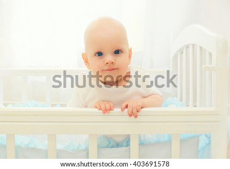Portrait little baby playing on the bed at home - stock photo