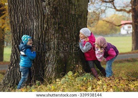 Portrait little children as they play hide and seek in the park - stock photo