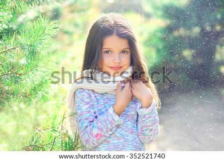 Portrait little girl child wearing a scarf and sweater near christmas tree - stock photo