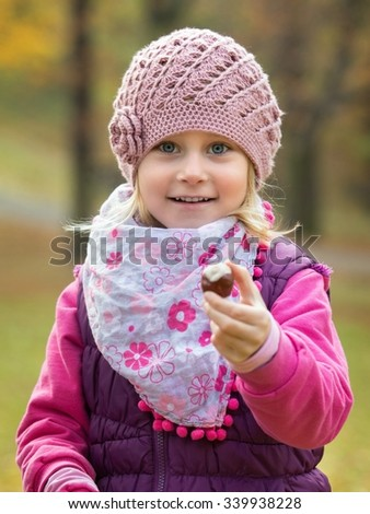 Portrait little girl in autumn park hold in hand chestnut - stock photo