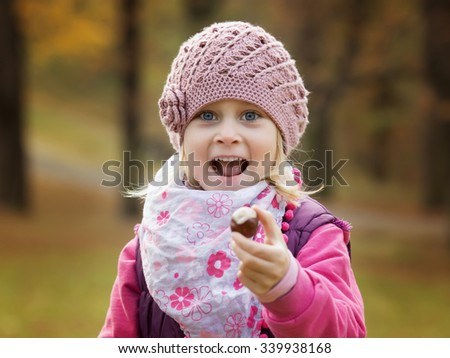 Portrait little girl in autumn parkto hold in hand chestnut - stock photo