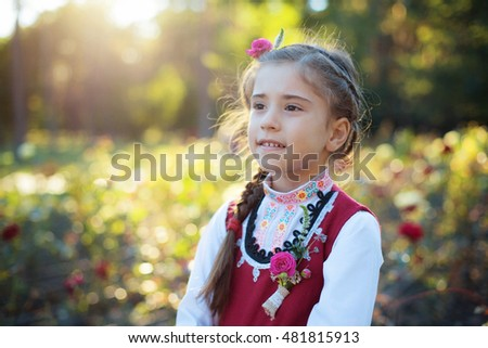 Portrait Little girl in traditional bulgarian cloth in garden in magic evening light. Festival of Roses Harvest in Valley of the Roses undertaken with great ceremony is notable Bulgarian holiday