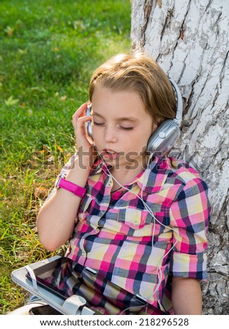 Portrait little girl sitting on grass near a tree and listening to the music using big headphones  in early autumn . - stock photo