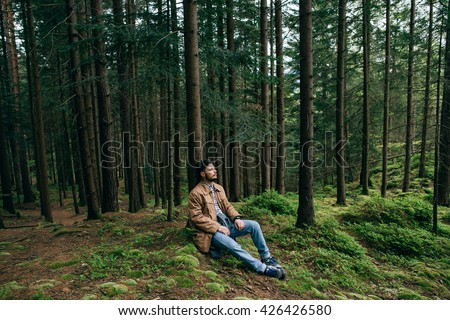 Portrait lonely bearded man hipster sits dream in mountain green forest - stock photo