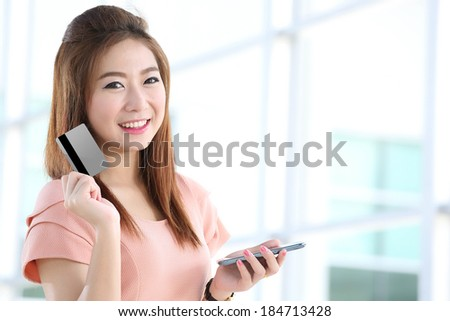 Portrait lovely girl type information with her  Credit card and  mobile phone  in Shopping mall