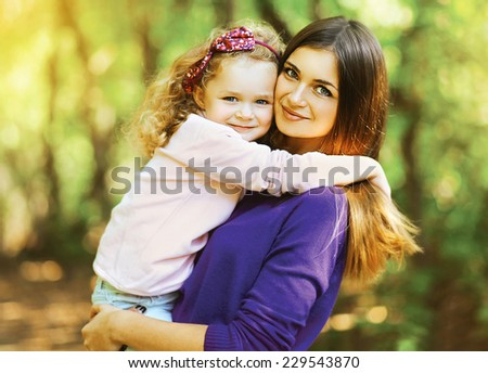 Portrait lovely mother and child together outdoors in sunny warm day - stock photo