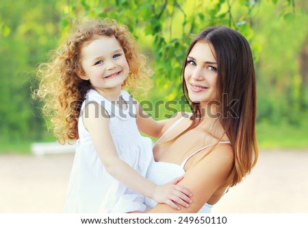 Portrait lovely young mother and cute daughter in sunny summer day - stock photo