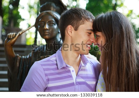 Portrait loving happy couple smiling and look each other in the eye in the summer sunny park - stock photo