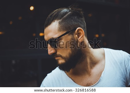 portrait macho sex appeal young guy with a beard and mustache and white T-shirt posing on the street vintage man, fashion men, hipster street   close-up - stock photo