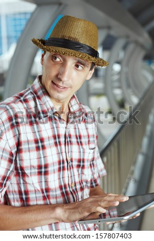 Portrait man at the outdoor in hat, with touchpad