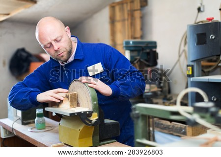Portrait man craftsman working with unfinished guitar indoors