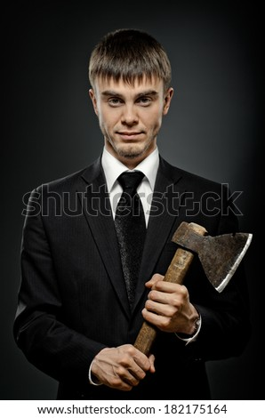 portrait  man in black costume and black necktie with axe, sinister look - stock photo