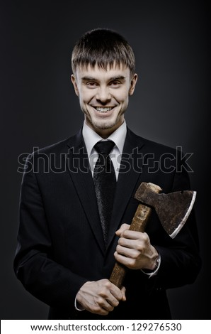 portrait  man  in black costume and black necktie with axe, sinister look and smile - stock photo