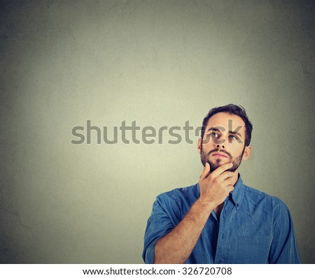 Portrait man thinking looking up isolated on gray wall background with copy space. Human face expressions, emotions, feelings, body language, perception - stock photo