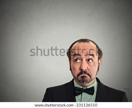 Portrait middle aged thoughtful man with puzzled facial expression looking up at copy space above head on grey wall background. Human emotions, body language, perception, vision, life situation  - stock photo