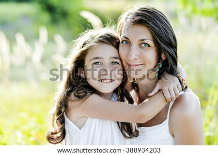 Portrait mother and daughter hugging. Nature, sunny weather