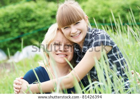Portrait mother and daughter in fold in one's arms and smiling at the outdoor - stock photo