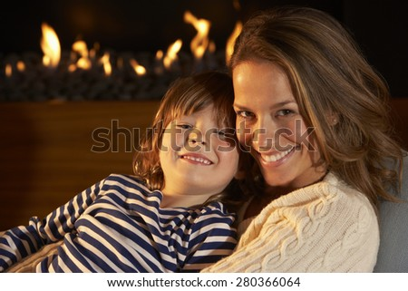 Portrait mother and son by firelight - stock photo