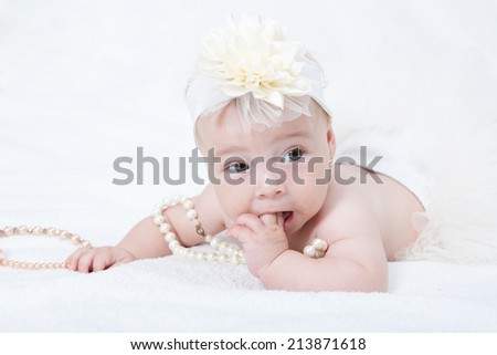 Portrait newborn baby lying in bed with a pearl necklace