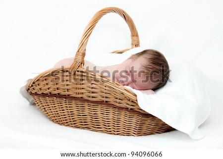 Portrait newborn baby sleeping in basket - stock photo