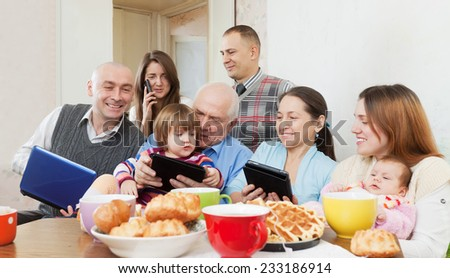 Portrait o Happy multigeneration family using electronic devices over tea  in home - stock photo
