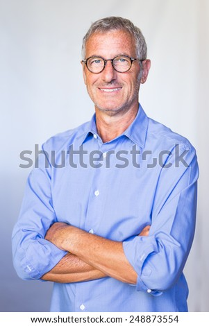 Portrait of a a successful mature handsome businessman smiling wearing a pair of glasses - stock photo