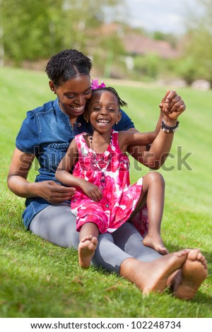 Portrait of a adorable african mother with her daughter in the garden - stock photo