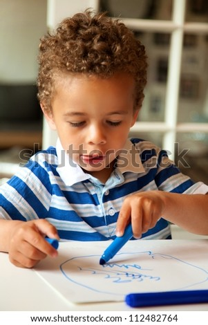 Portrait of a adorable little boy drawing something on paper - stock photo