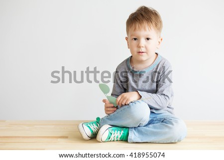 Portrait of a adorable little kid with blue paper glasses against a white background. - stock photo