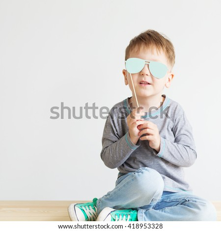 Portrait of a adorable little kid with blue paper glasses against a white background. A blind child - stock photo