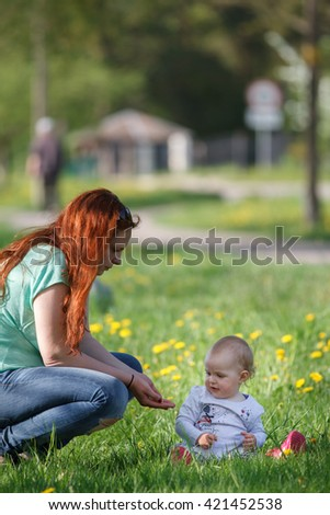 Portrait of a adorable mother with her daughter in the garden - stock photo