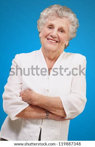 portrait of a adorable senior woman standing over blue background
