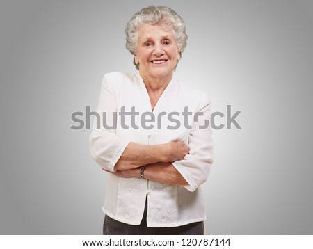 portrait of a adorable senior woman standing over grey background - stock photo