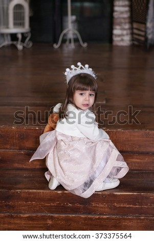 portrait of a adorable 2-year-old girl in interior.  Little Princess is hurt - stock photo