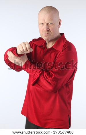 Portrait of a adult white bald man in a red shirt with a cross on his chest on a light background studio - stock photo