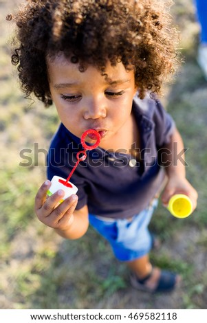 Portrait of a african american baby blowing soap bubbles in the park.
