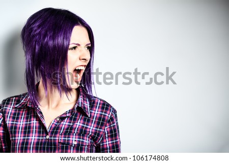 Portrait of a aggressive punk girl with purple hair. - stock photo