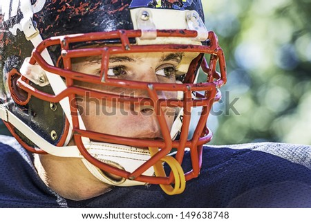 Portrait of a American Football Player with a heavily worn helmet - stock photo
