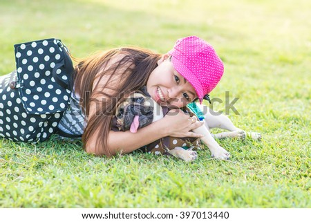 Portrait of a asian teenage woman girl hug with her cute dog puppy pug outdoors on fields - stock photo