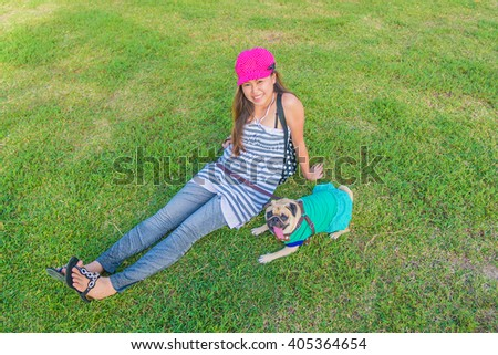 Portrait of a asian teenage woman girl sit rest with her cute dog puppy pug outdoors on fields - stock photo