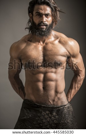 Portrait of a athleltic muscular bearded man posing on a grey background - stock photo