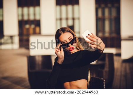 portrait of a attractive woman holding a smartphone digital camera with her hands and taking a selfie self portrait of herself . Travel and technology outdoors. - stock photo