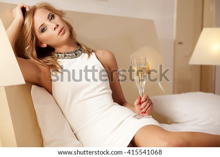 Portrait of a attractive young adult beautiful blonde lady in white elegance dress drinking champagne on the bed in luxury apartment