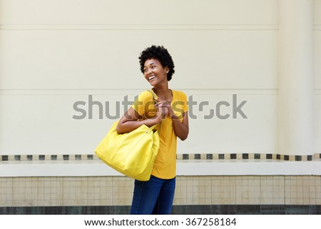 Portrait of a attractive young african woman with bag looking away and smiling - stock photo