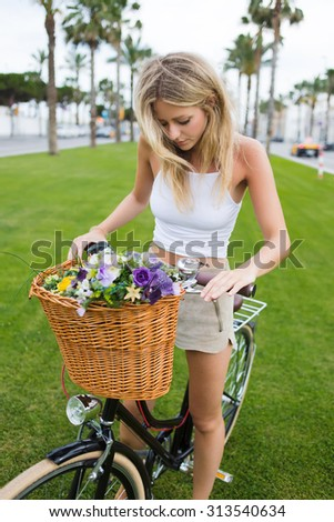 Portrait of a attractive young blonde woman preparing for ride in the park on her classic bicycle, pretty female in stylish clothes enjoying weekend strolling on vintage bike with basket of flowers - stock photo