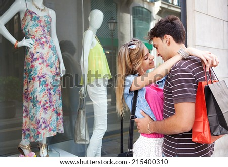 Portrait of a attractive young couple having fun together and enjoying a vacation city break, embracing and smiling while shopping in the fashion stores, outdoors. Consumer and travel lifestyle. - stock photo
